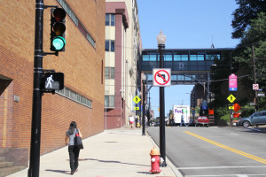 A pedestrian walks past the new traffic light, pole and pedestrian signal on Forbes Avenue near Rockwell Hall. In total, the university, in conjunction with the city, installed 13 poles, 20 traffic lights and 22 pedestrian crossing signals.