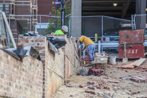 Construction workers use recycled bricks from the recently demolished Bagamoyo building between the A.J. Palumbo Center and the existing Forbes Avenue garage to erect a retaining wall for the temporary lot.