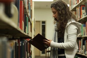 Photo by Claire Murray   The Duquesne Duke. Freshman early childhood education major Elizabeth Osche picks out a book in the Gumberg Library. Students who want to read for pleasure can visit the McNaughten Popular Book Collection across from the front desk at the library.