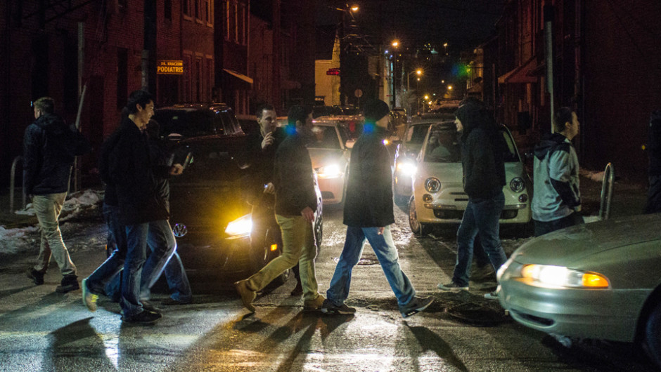 Photo by Aaron Warnick | Photo Editor. A group of walkers cross the street Saturday night on East Carson Street in South Side. The city of Pittsburgh, in collaboration with the Responsible Hospitality Institute, is implementing new procedures to make the neighborhood safer at night.