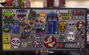 (Aaron Warnick / Photo Editor) - Stickers and magnets made from Perler beads representing some of the many fandoms that attended the convention.