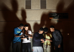 AP Photo. Saudi youths view their pictures after taking photographs of the Kingdom Tower with its lights turned off during the worldwide Earth Hour Saudi Arabia on March 29.