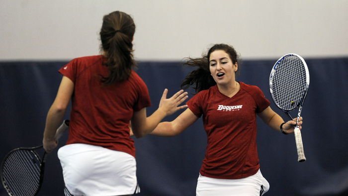 Courtesy of Athletic Department Senior captain Chandler Consonery (right) and junior Alexa Miller (left) high-five after a point earlier this season. Consonery is 7-7 in singles competition and 10-3 in doubles play this year.