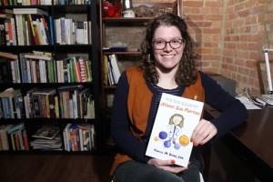 "In this Feb. 5, 2015 photo, Veronica Berns holds the comic book ""Atomic Size Matters"" that she created to explain her doctoral chemistry thesis to her family at her apartment in Chicago. Berns, a comic book fan, says the illustrations are not well-polished because she wanted it to be like she was explaining on the back on an envelope. She ended up raising more than twice what she asked for on the crowd funding website Kickstarter to print the book. (AP Photo)"