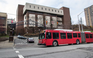 Photo By Claire Murray| Photo Editor. A bus passes the entrance to Duquesne University on Forbes Avenue. The city wants to collaborate with the Unviersity in its efforts to transform Uptown.
