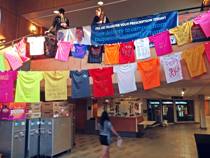 "Kaye Burnet | Asst. News Editor. Colorful t-shirts hang on clothes lines in the Union lobby, sporting anti-rape slogans such as ""No Means No"" and ""Put the Red Light on Domestic Violence."" The display is part of Duquesne's participation in Sexual Assault Awareness Month."
