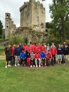 Members of the Duquesne men's basketball team pose alongside Coach Jim Ferry in front of Ashford Castle near Cong, Ireland.