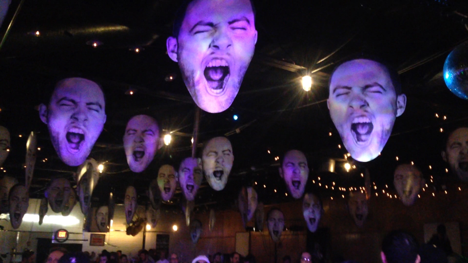 "Photo by Julian Routh | Editor-in-Chief. Cutouts of Mac Miller's head hang from the ceiling at Spirit in Lawrenceville during the rapper's surprise album release party last Friday night. Read more about Mac's homecoming weekend and his major label debut, ""GO:OD AM,"" on page 9."
