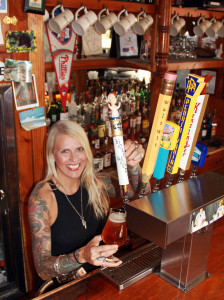In this photo taken Sept. 11, 2015 and provided by the Philadelphia Brewing Company, Marianne Morrison pours a glass Holy Wooder at Atlantis the Lost Bar in Philadelphia. The beer was inspired by Pope Francis' visit to Philadelphia. (Cameron Blyth/Philadelphia Brewing Co. via AP)