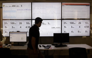 AP- In this Sept. 9, 2015 file photo, an employee in the software development department of DraftKings, a daily fantasy sports company, walks past screens displaying the company's online system stats in Boston. Customers of the two biggest daily fantasy sports websites have filed at least four lawsuits against the sites in Oct. 2015, following cheating allegations and a probe into the largely-unregulated multi-billion dollar industry. In court papers, the customers accused the DraftKings and FanDuel sites of cheating, and argued they never would have played had they known employees with insider knowledge were playing on rival sites. (AP Photo/Stephan Savoia)