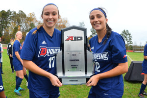 Courtesy of the Athletic Department. Juniors Maggie Mayo and A.J. Baroffio pose with the Atlantic-10 trophy.