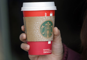 A customer carries a coffee drink in a red paper cup, with a cardboard cover attached, outside a Starbucks coffee shop in the Pike Place Market, Tuesday, Nov. 10, 2015, in Seattle. It's as red as Santa's suit, a poinsettia blossom or a loud Christmas sweater. Yet Starbucks' minimalist new holiday coffee cup has set off complaints that the chain is making war on Christmas. (AP Photo/Elaine Thompson)