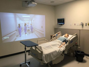 Courtesy Photo A simulation video plays in one of the mock hospital rooms in Libermann Hall. Nursing students now have a space to practice responding to medical situations.