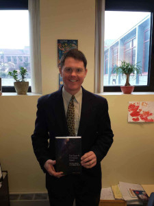 By Raymond Arke | The Duquesne Duke Theology professor Daniel Scheid poses with a copy of his new book, which explores links between major religions and caring for the environment.