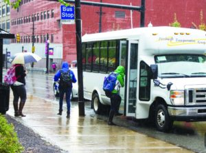 Claire Murray / The Duquesne Duke In this fall 2015 file photo, a Duquesne student boards the South Side Shuttle bus on Forbes Avenue. Some students have complained that the bus runs late, the app is hard to follow and drivers take lengthy stops while students wait inside the bus.