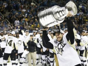 FILE - In this June 12, 2016, file photo, Pittsburgh Penguins center Sidney Crosby raises the Stanley Cup after Game 6 of the NHL hockey Stanley Cup Finals against the San Jose Sharks in San Jose, Calif. The Penguins will raise their fourth Stanley Cup banner to the rafters before Thursday night's opener against Washington, and do it in front of a Capitals' team that is growing tired of watching other clubs celebrate championships.   (AP Photo/Marcio Jose Sanchez, File)