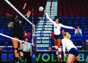 Courtesy of Duquesne Athletics  | Liz Wayne rises up as she tries to dump an attack attempt over the VCU blockers.