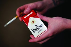FILE - In this July 17, 2015, file photo, store manager Stephanie Hunt poses for photos with a pack of Marlboro cigarettes, an Altria brand, at a Smoker Friendly shop in Pittsburgh. Altria Group reports financial results on Wednesday, Feb. 1, 2017. (AP Photo/Gene J. Puskar, File)